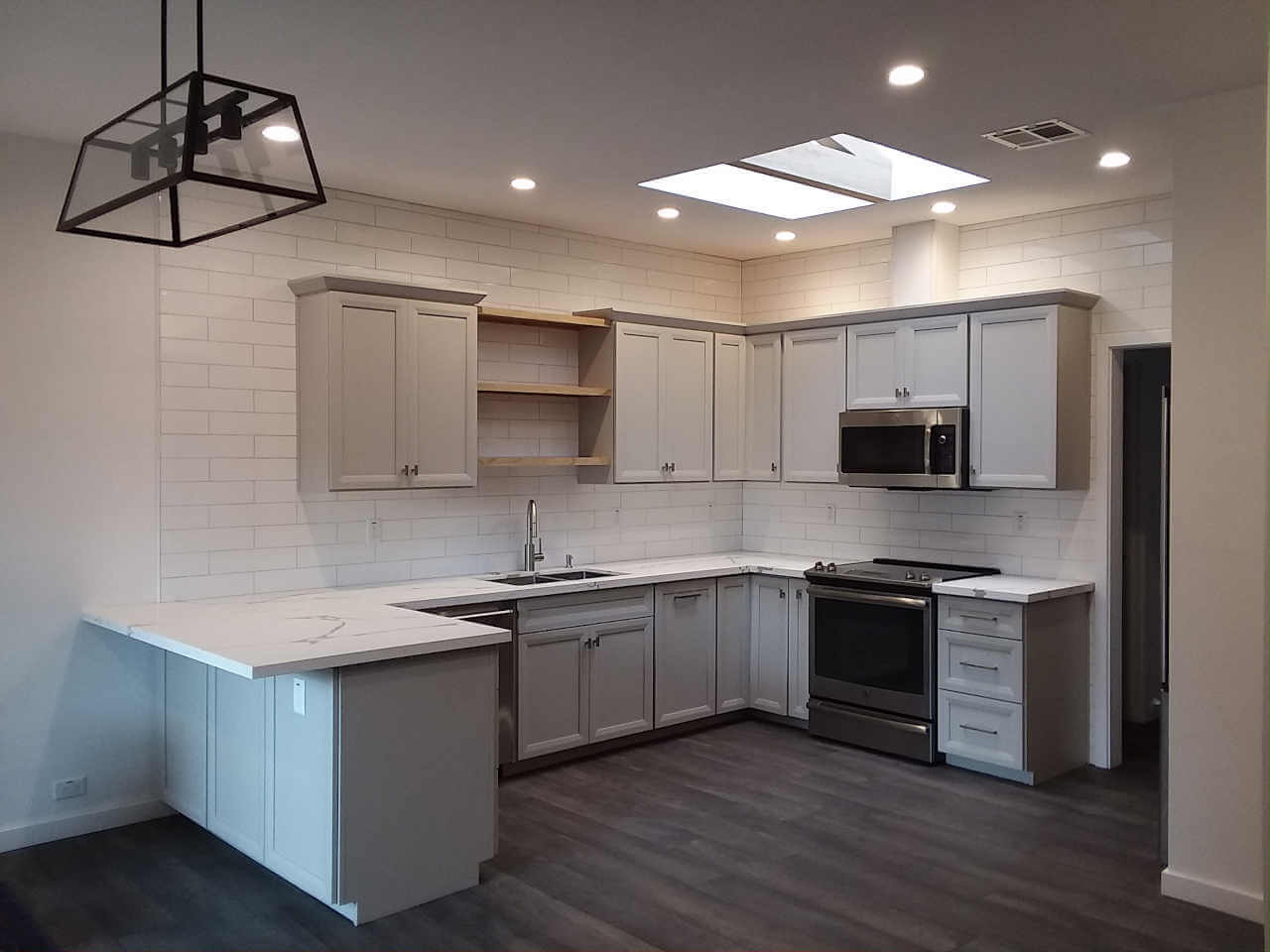 Custom gray kitchen cabinets, quartz countertops and subway tile backsplash