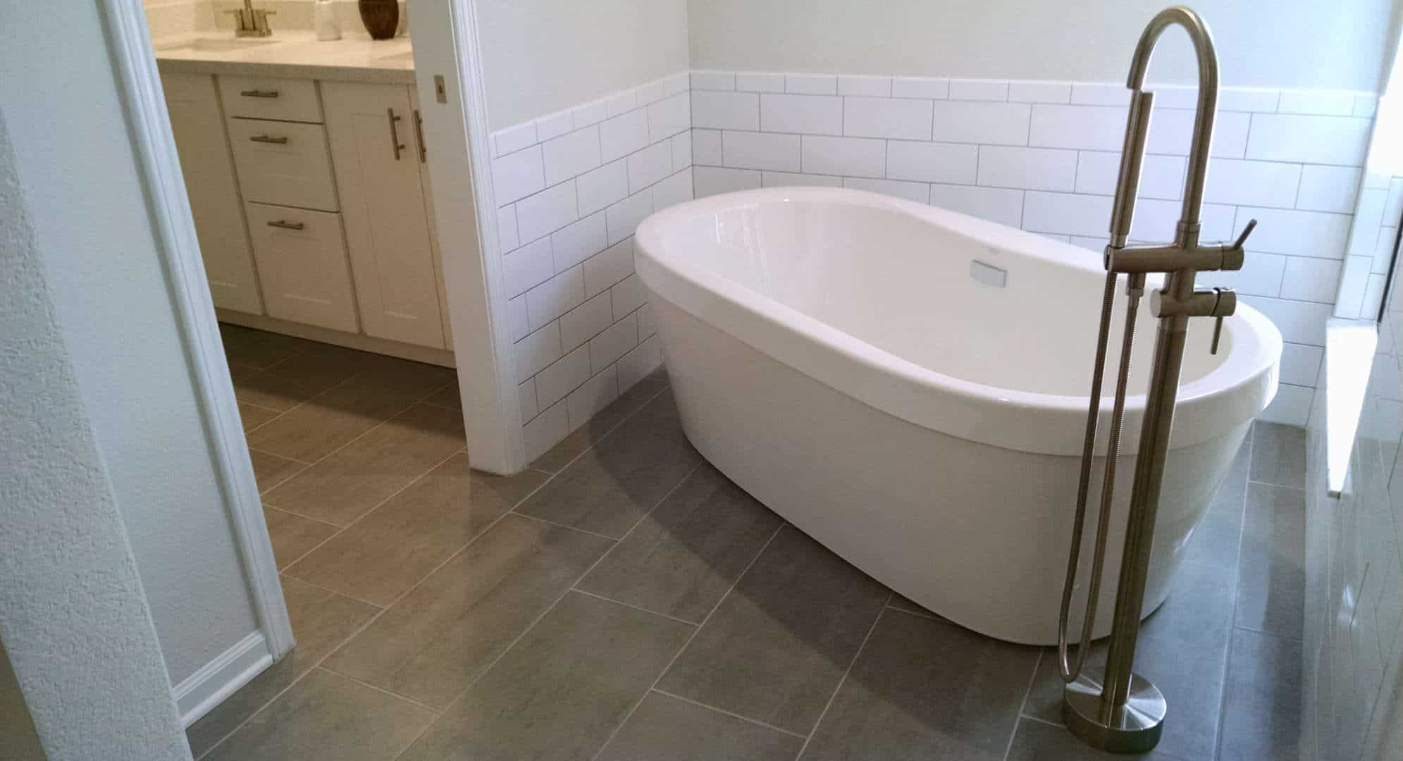white free standing bathtub on gray tile floor