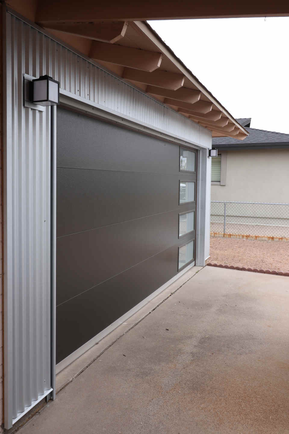 modern garage with metal siding and clopy modern door
