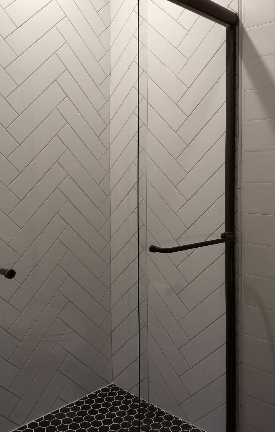 white herringbone shower with black floor and black door frame