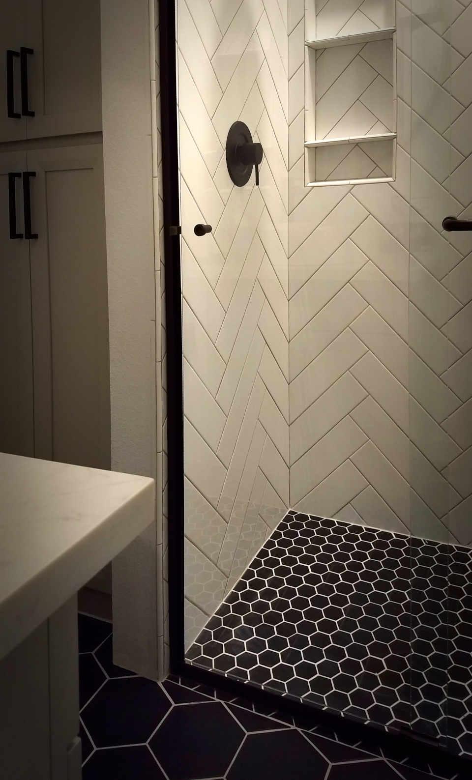 white herringbone tile shower with black hex floor